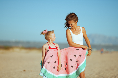 modern mother and child in swimwear wrapped in funny watermelon towel on the seashore in the evening looking at each other. blond hair child in red dotted swimsuit with flowers. modern european mother