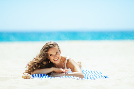 Portrait of happy healthy woman in white beachwear on the ocean shore lying on a striped towel. protect your hair from sun, heat, and humidity before heading to the beach. quiet vacation heaven.