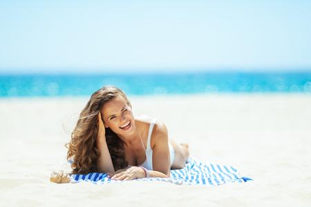 uśmiechający się sprawny kobieta w białych strojach kąpielowych nad brzegiem morza, leżąc na ręczniku w paski. dostawanie witaminy D po długich zimowych miesiącach. całkowity relaks na najlepszej plaży. Włosy chronione przed słońcem. Zdjęcie Seryjne