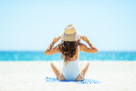 Seen from behind trendy woman in white swimsuit sitting on a striped towel on the seacoast. woman wearing straw hat. Covering up with a hat to avoiding the harsh summer midday sun. Archivio Fotografico - 115931695