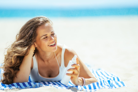 smiling trendy woman in white beachwear with SPF laying on a striped towel on the ocean shore. sunscreen hight SPF with broad range UV UVB for maximum sunburn protection or hair protection conditioner
