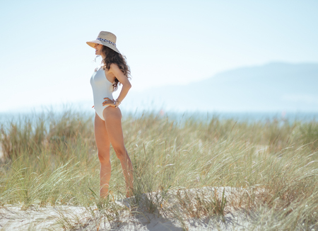 Full length portrait of happy young woman in white swimwear on the seashore looking into the distance. woman waring straw hat for sun protection. wild beach with green grass and no people. blue sky. Banco de Imagens