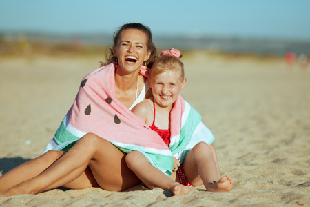 happy modern mother and daughter in beachwear on the seashore in the evening wrapped in funny watermelon towel sitting on sand. Sun protected hair. blond hair young lady.