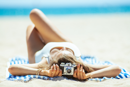 Seen from behind retro photo camera holding by woman laying on a striped towel on the ocean shore. Capture vacation in incredible photos preserve those memories or share beach vacation with family. Foto de archivo - 115931713