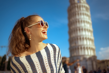 Portrait of smiling elegant woman in striped blouse near leaning tower in Pisa, Italy looking into the distance. classic example of overtourism. solo traveler. blue sky. european woman.