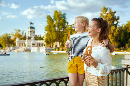 smiling trendy mother and daughter tourists with traditional Spain churro looking into the distance at Park del Retiro. churros - classic Madrid sweet snack. family trip to Madrid. blue sky.