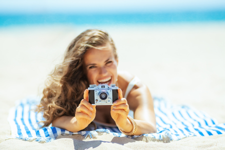Closeup on retro photo camera holding by woman laying on a striped towel on the seacoast. Capture vacation in incredible photos to relive those good times and share with family and friends. Foto de archivo - 115931808
