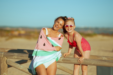 Portrait of happy young mother and daughter in swimsuit on the beach in the evening. mother and daughter near a wooden fence. minimal to no crowd peace.