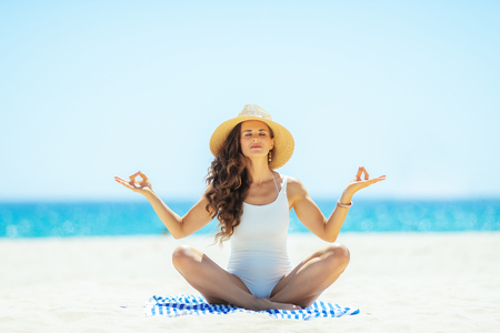 relaxed modern woman in white swimsuit doing yoga while sitting on a striped towel on the seashore. woman in straw hat. Hair healthy condition. quiet vacation heaven. total relaxation on the beach Stock Photo