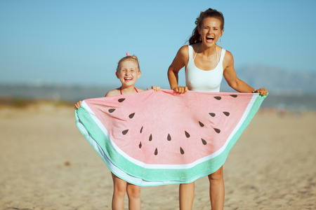 cheerful young mother and child in beachwear on the beach in the evening holding funny watermelon towel. blue sky. protect your hair from sun, heat, and humidity before heading to the beach.
