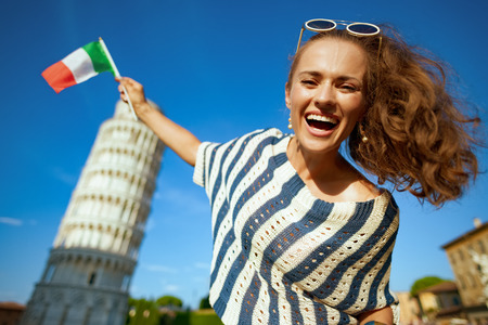 smiling elegant woman in striped blouse puts a flag on leaning tower in Pisa, Italy. taking silly photographs is a must here. solo traveler. blue sky. having micro trip. Sunny summer midday.
