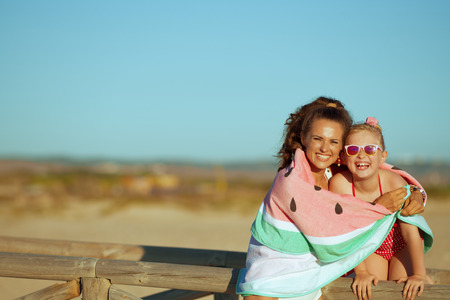 Portrait of happy young mother and daughter in beachwear on the beach in the evening wrapped in watermelon towel. mother and daughter hugging near wooden fence. A day at the beach can be awesome.