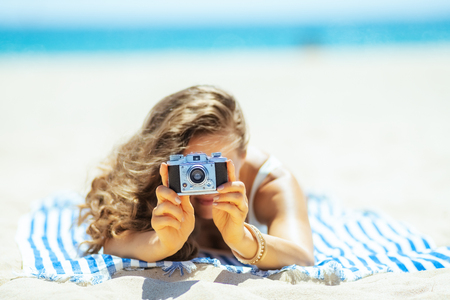 Closeup on retro photo camera holding by woman laying on a striped towel on the seashore. Capture vacation in incredible photos preserve those memories and share with family and friends & on social. Foto de archivo - 115932063