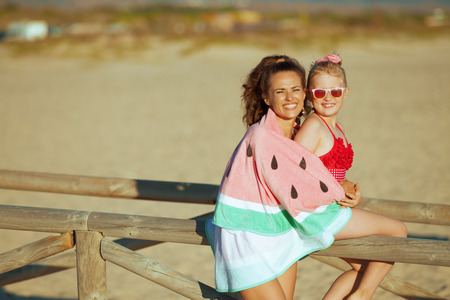 smiling modern mother and daughter in swimwear on the ocean shore in the evening wrapped in watermelon towel. mother and daughter near a wooden fence. Sun protected hair. spending hours at the beach