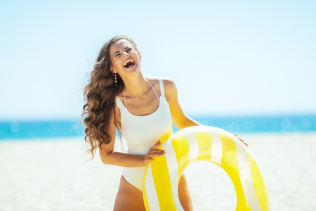 happy healthy woman in white swimwear on the ocean coast holding yellow inflatable lifebuoy. protect your hair from sun, heat, and humidity before heading to the beach. Sun protected hair. 写真素材