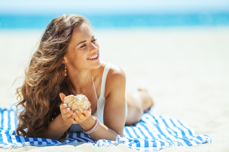 relaxed healthy woman in white swimsuit with seashell laying on a striped towel on the seacoast. successful shelling on vacation at the beach. stressed free beach retreat. Sun protected hair Stock Photo