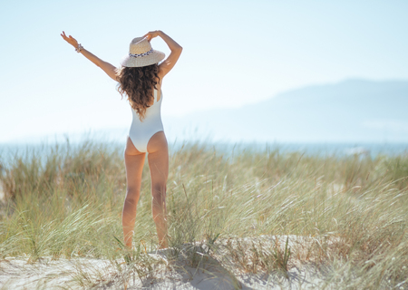 Seen from behind young woman in white beachwear on the beach rejoicing. woman waring straw hat for sun protection. quiet vacation heaven. european woman long wavy hair brunette 30 something years old