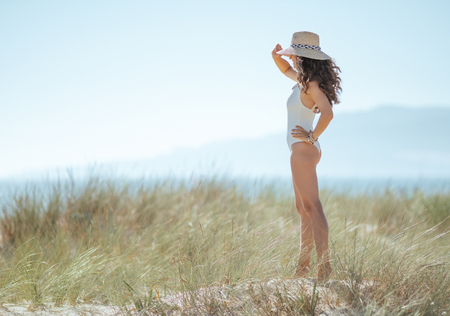 Full length portrait of modern woman in white beachwear on the beach looking into the distance. woman waring straw hat for sun protection. blue sky. carefree beach fun. quiet vacation heaven. 스톡 콘텐츠