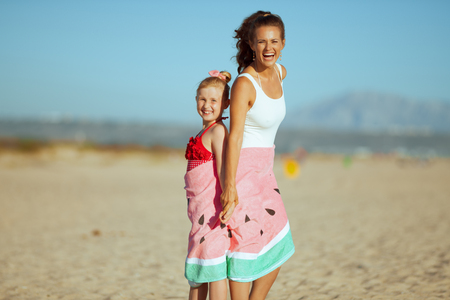 happy young mother and daughter in swimsuit on the ocean coast in the evening wrapped in watermelon towel. beach time - perfect way to be active and outside with your kids. Stock Photo