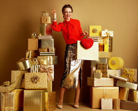 Happy modern fashion-monger in red blouse and golden sparkly sequin pencil skirt with shopping bag and red heart fingers snapping among 2 piles of golden gifts in front of a plain wall.Valentine's Day