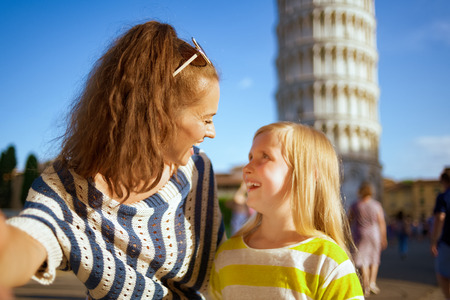 smiling modern mother and daughter taking selfie against leaning tower in Pisa, Italy. classic place to take photos for social media platform. daughter with blond hair . well know touristed path. 免版税图像