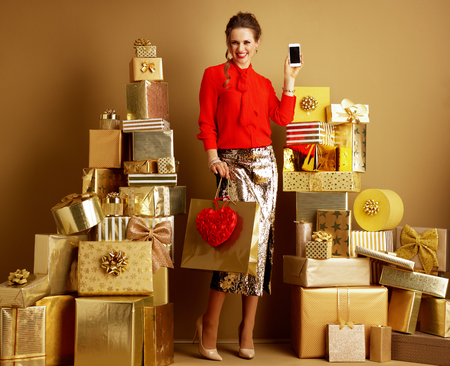 Happy stylish fashion-monger in red blouse and golden sparkly sequin pencil skirt with shopping bag and red heart showing cellphone blank screen among 2 piles of golden gifts. Valentines Day. Stock fotó