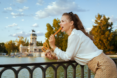 happy modern tourist woman in white blouse and shorts in Madrid, Spain eating traditional Spain churro. churros - classic Madrid sweet snack. woman travel alone. perfect destination choice.solo travel