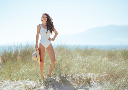 Full length portrait of young woman in white swimwear on the beach.woman holding straw hat. stressed free beach retreat. quiet vacation heaven. minimal to no crowd peace. european woman. blue sky. Banco de Imagens - 115932250