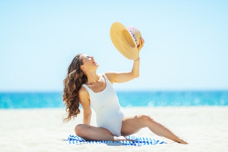 Portrait of cheerful trendy woman in white beachwear sitting on a striped towel on the seacoast. woman holding straw hat. Hair healthy condition. total relaxation on the best beach vocation 版權商用圖片