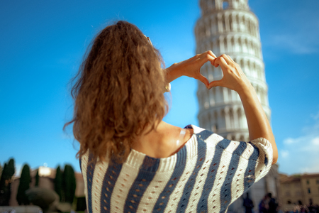 Seen from behind young woman in striped blouse showing heart shaped hands against leaning tower in Pisa, Italy. having micro holidays. can't avoid crowds here. blue sky. Sunny summer midday.