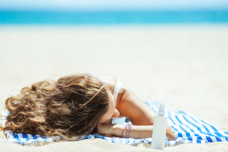 healthy woman in white beachwear with suntan lotion laying on a striped towel on the seacoast. sunscreen SPF or bug repellent or insect bite remedy or hair protection leave-in SPF conditioner.