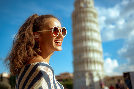 happy young woman in sunglasses and striped blouse looking into the distance against leaning tower in Pisa, Italy. Sunny summer midday. well know touristed path. having micro holidays. european woman 版權商用圖片