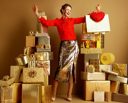 Full length portrait of happy trendy fashion-monger in red blouse and golden sparkly sequin pencil skirt with shopping bag and red heart rejoicing among 2 piles of golden gifts. Valentine's Day. Stock Photo
