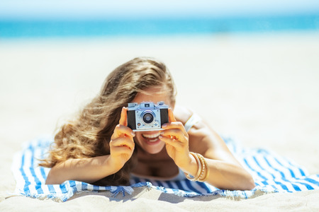 Closeup on retro photo camera holding by woman laying on a striped towel on the ocean shore. Capture vacation and share beach vacation with family and friends and on social media platforms. Foto de archivo - 115932518