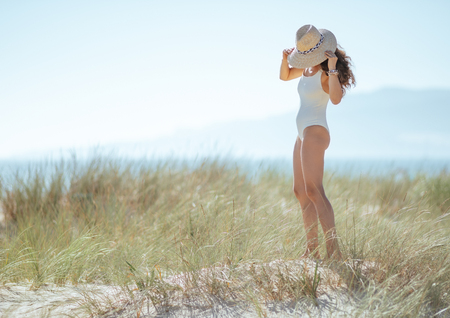 Full length portrait of modern woman in white swimsuit on the ocean coast wearing hat. woman waring straw hat for sun protection. wild beach with green grass and no people. carefree beach fun.