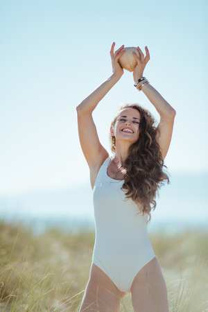 smiling young woman in white swimsuit on the beach rising coconut. Coconut oil as a leave-in treatment to repair split ends, moisturize your scalp, and add a healthy glow to your tresses. blue sky. Stock Photo