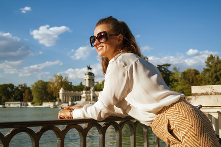 happy stylish woman in white blouse and shorts at El Retiro Park in Madrid, Spain looking into the distance. blue sky. solo traveler. �aucasian woman 30 something years old. having micro trip. summer Stockfoto