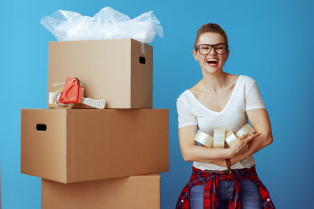 happy young woman in white t-shirt near cardboard box with a lot of adhesive tapes isolated on blue background