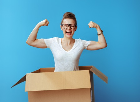 happy young woman in white t-shirt showing biceps in a cardboard box isolated on blue background Stock Photo