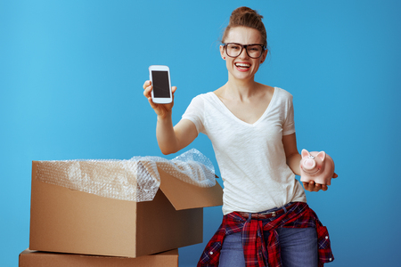 smiling young woman in white t-shirt with piggybank showing phone blank screen near cardboard box isolated on blue. Call professional movers and obtain quotes from several different moving companies.