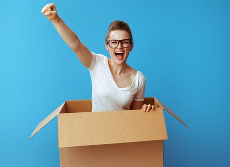 excited young woman in white t-shirt pops out of a cardboard box isolated on blue background Banco de Imagens