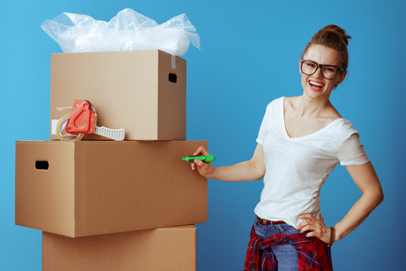 happy young woman in white t-shirt signs cardboard box isolated on blue. woman labeling cardboard box with green color permanent marker on side of a box