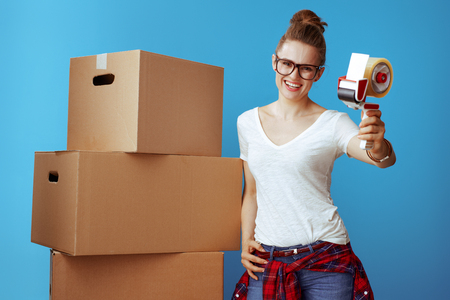 smiling young woman in white t-shirt near cardboard box giving tape dispenser on blue background. Time is money get yourself good packing and moving supplies.