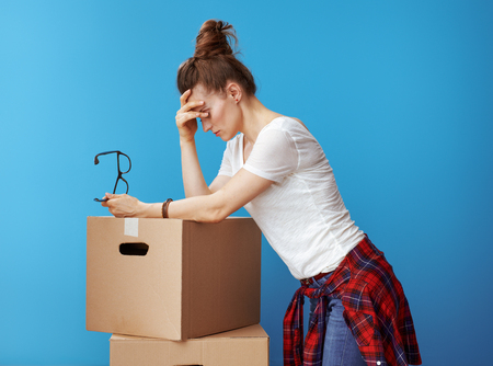 stressed modern woman in white t-shirt near cardboard boxes against blue background