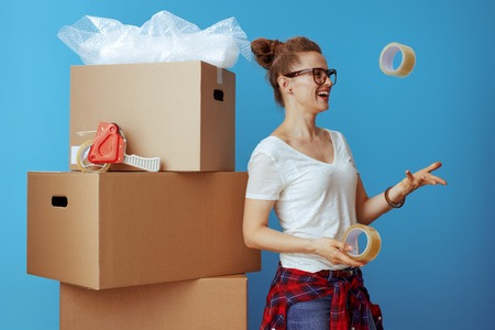smiling modern woman in white t-shirt near cardboard box throwing up adhesive tapes isolated on blue Stock Photo