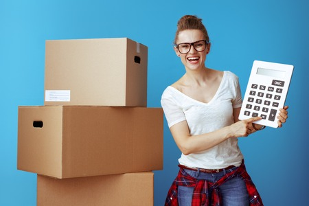 happy modern woman in white t-shirt near cardboard box with calculator isolated on blue background. Economy way to move to new location.