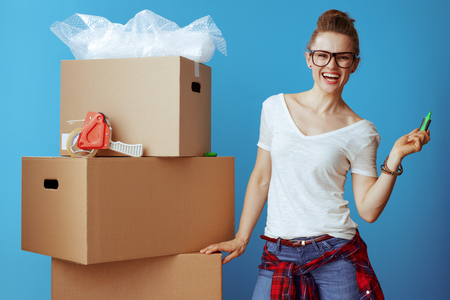 happy young woman in white t-shirt near cardboard box with a marker isolated on blue background. keep yourself organized on moving day and label clearly on the top and side of each box
