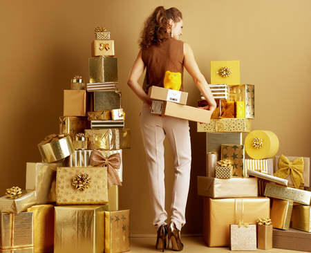 Seen from behind elegant woman in gold beige pants and brown blouse with parcels and yellow piggy bank among 2 piles of golden gifts. e-commerce low cost faster holiday shipping.