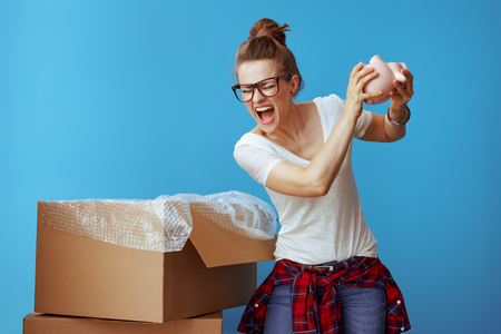 annoyed modern woman in white t-shirt wants to break a piggybank on blue background. Moving can be very stressful and money consuming, but I have to move to a new location. Stock Photo