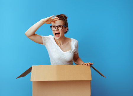 happy young woman in white t-shirt looking into the distance in a cardboard box isolated on blue